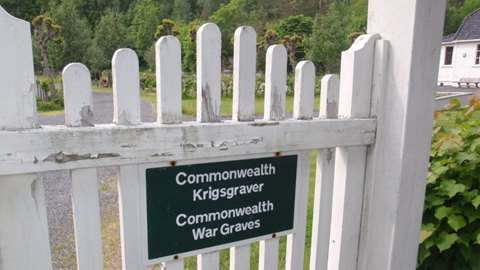 "Picture of a white wooden gate at Risør war cemetery with a black sign with the following text: ""Commonwealth Krigsgraver / Commonwealth War Graves""."