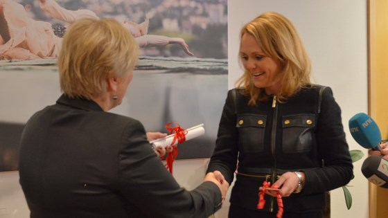 Former Minister of Culture Thorhild Widvey hands over the keys to her office to Linda Cathrine Hofstad Helleland.