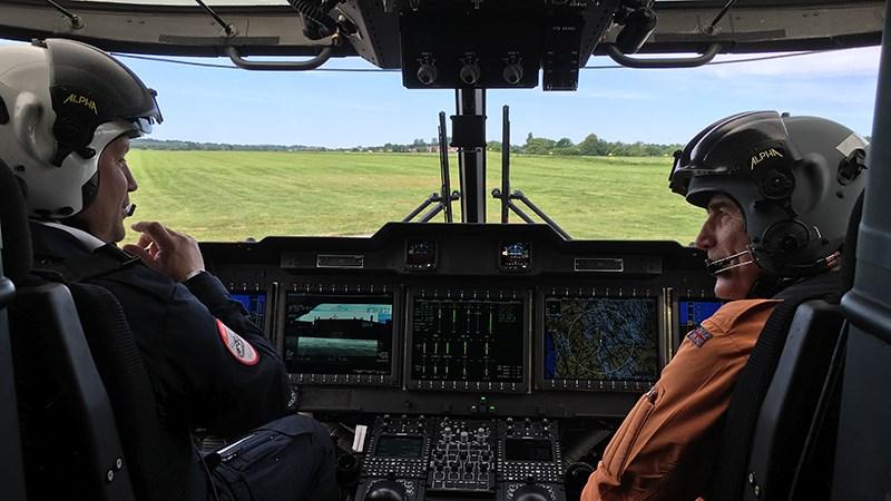 Justis- og beredskapsministeren i samtale med en pilot i redningshelikopteret.