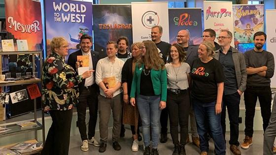Gruppebilde fra presentasjonen av dataspillstrategien. Gruppen står foran plakater med ulike spillselskaper.
