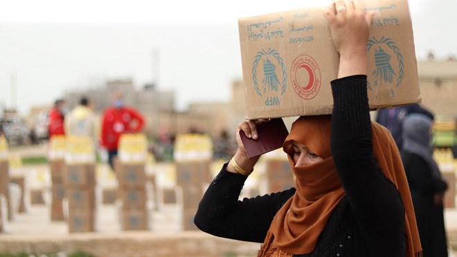 A woman collects food in Deir Hafer, 60 km from Aleppo in Syria. WFP is working with the Syrian Arab Red Crescent to distribute food to the most vulnerable and ensure that families are aware of COVID-19 and safety measures. Credit: WFP/Khudr Alissa
